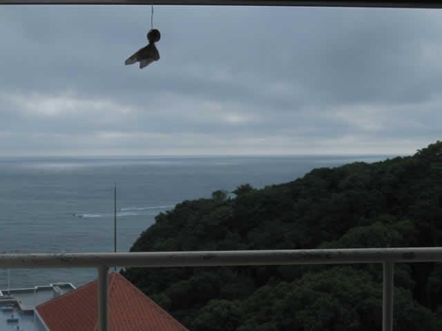 写真2:ホテルの部屋の窓の外は物憂げな曇り空です。雨が降りそうな写真です。