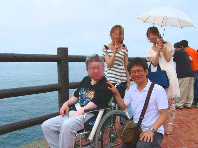 写真5:波が打ち寄せる海岸を、お客様はヘルパーと一緒に車椅子でゆっくりと進んでいます。岸壁に手が届きそうです。