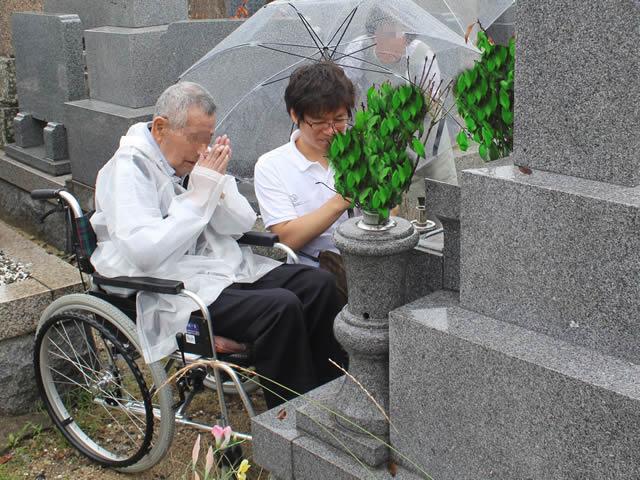 写真6:車椅子に乗り、お墓の前で手を合わせるお客様とエスコートヘルパーの写真です。
