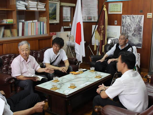 写真8:小学校の校長室での写真です。校長先生や教頭先生とお話しています。