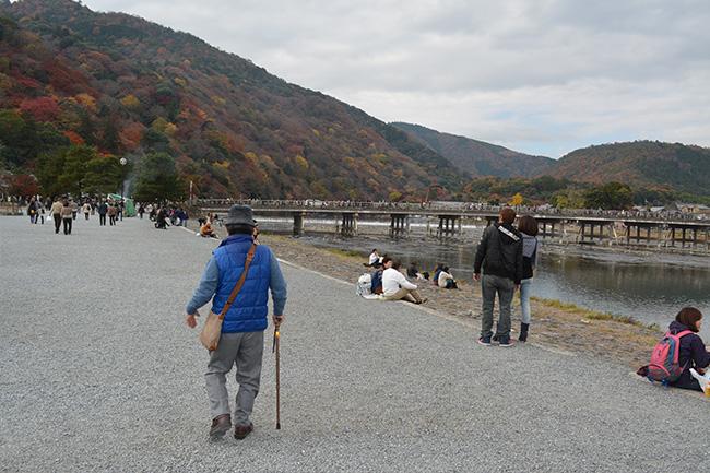 写真:杖を使いゆっくりと桂川沿いを歩くお客様