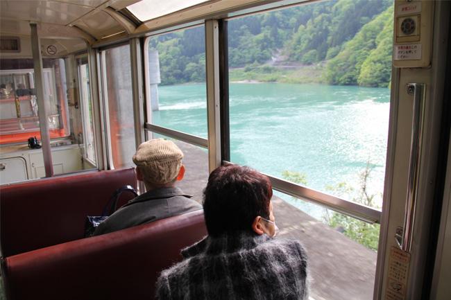 写真:黒部峡谷トロッコ電車の車窓を楽しむお客様