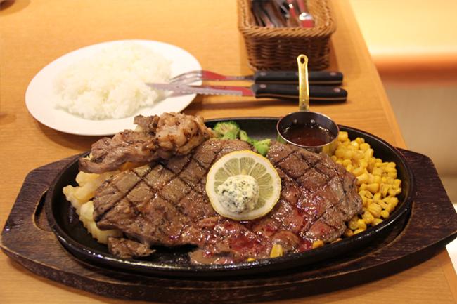 写真:熱々の鉄板で運ばれてきたステーキ