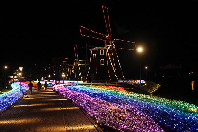 写真:虹色の道とイルミネーションで飾られた風車
