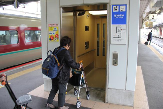 写真:シルバーカーを押しながら、駅ホームのエレベーターに