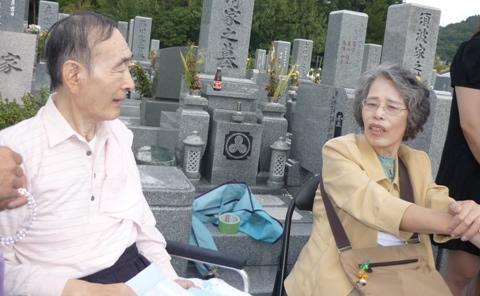 写真:お墓の前で話す二人