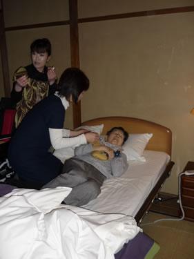 写真:エスコートヘルパーがベッドで介助中。