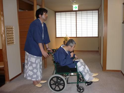 写真:車いすに座るお客さん。それを押すエスコートヘルパー。二人とも浴衣。