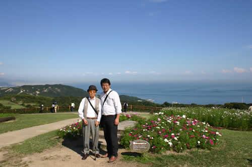 写真:あわじ花さじきで海を背景にエスコートヘルパーと記念撮影