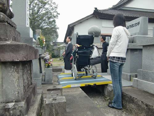 写真:お墓の前でお寺とともに手をあわす