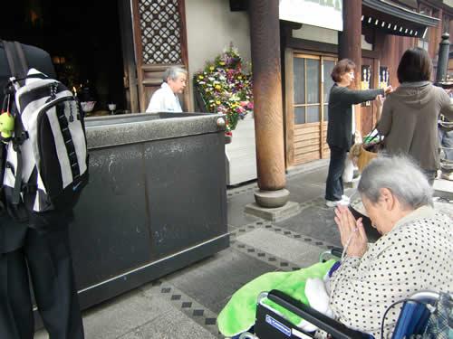写真:本堂と納骨堂の前で長い間手を合わせる