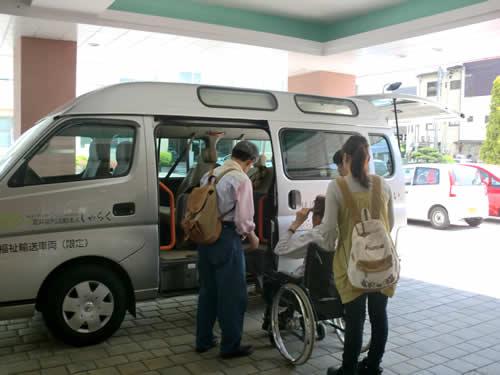 写真:家族と一緒にタクシーに乗り込む