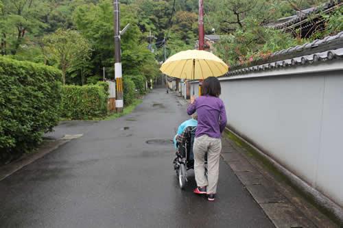 写真:雨が降る中、傘を持って移動