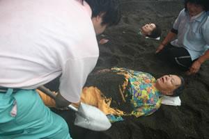 写真:Sさん砂蒸し風呂へ。服のまま土をかけられる。